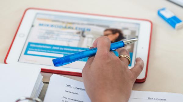 Termine (im Bild: eine Hand hält einen Stift und bedient gleichzeitig ein Tablet).