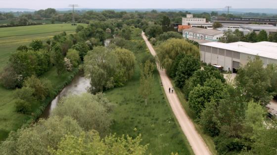 Erfolgsgeschichte Klima Invest (zu sehen ist eine Landschaft am Fluss mit einem Fahrradweg)