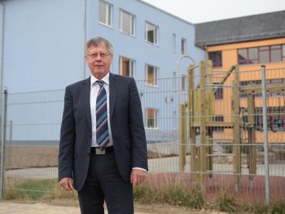 Thomas Fügmann, Landrat Saale Orla Kreis, setzte sich entscheidend für die Umsetzung des Schulzentrum-Projektes als ÖPP-Projekt ein. (im Bild: Thomas Fügmann vor dem Schulneubau)