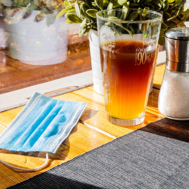 Neue Corona-Hilfen für temporäre Schließungen im November (im Bild: ein Mund-Nasen-Schutz auf einem Tisch neben einem Getränk).