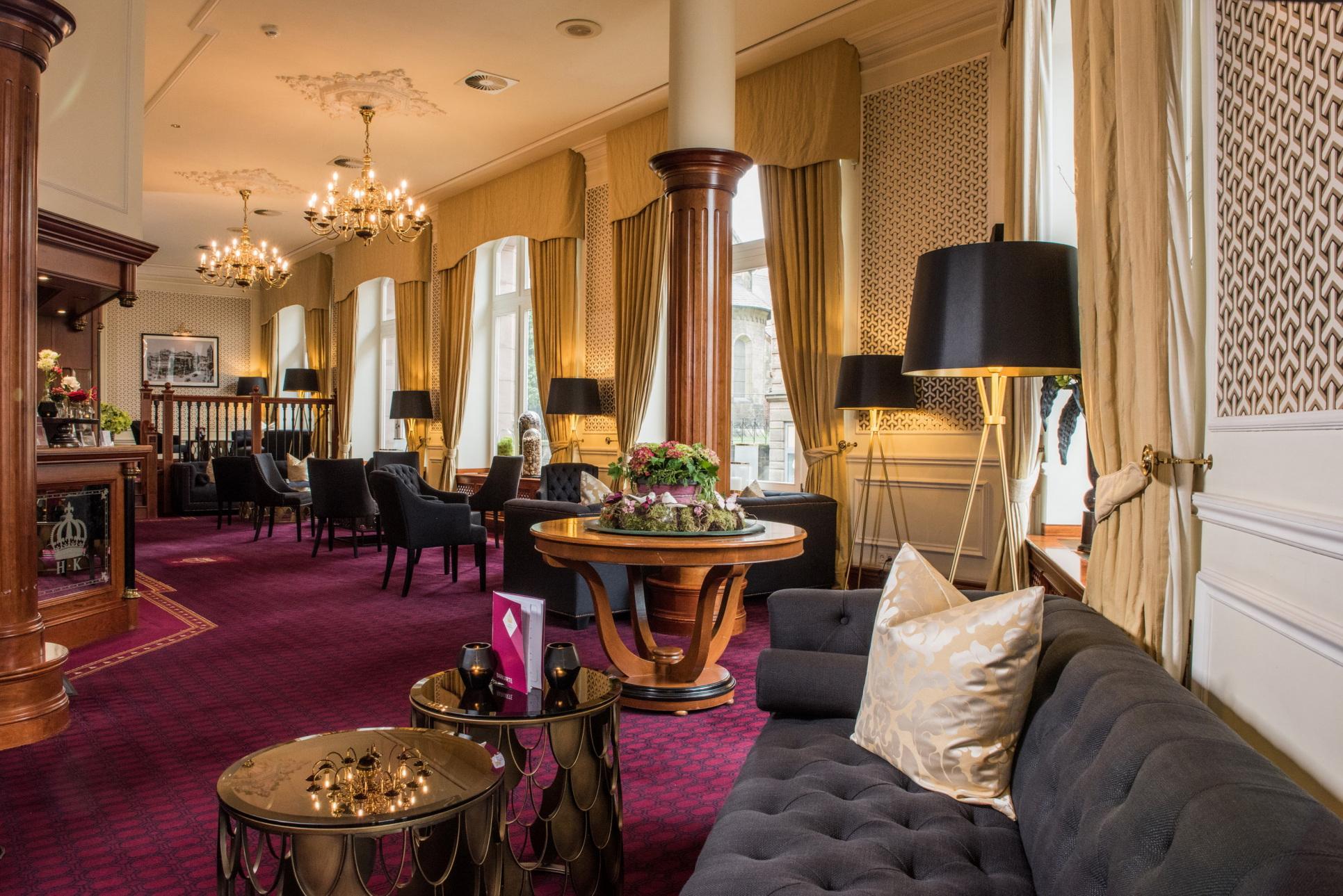 #Zuversicht: Kaiserhof und Glockenhof (im Bild: die Lobby des Kaiserhofs mit dunkel gehaltenen Möbeln, rotem Teppich und hellen Vorhängen)