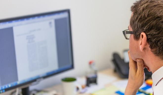 Gefälschte E-Mails zur Corona-Soforthilfe im Namen der TAB (im Bild: Mitarbeiter schaut auf einen Computerbildschirm).