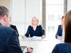 Aktuelle Informationen für Steuerberater*innen (im Bild: Menschen in einer Besprechung, in der Mitte eine Frau mit Aktenordner).