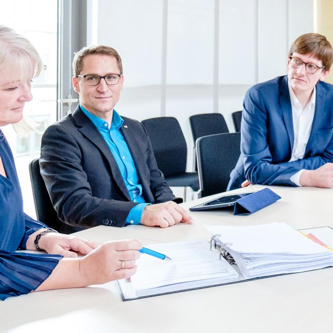 Haushaltskonsolidierungsberatung (im Bild: drei Mitarbeiter*innen der TAB beugen sich über Unterlagen und sind im Gespräch)
