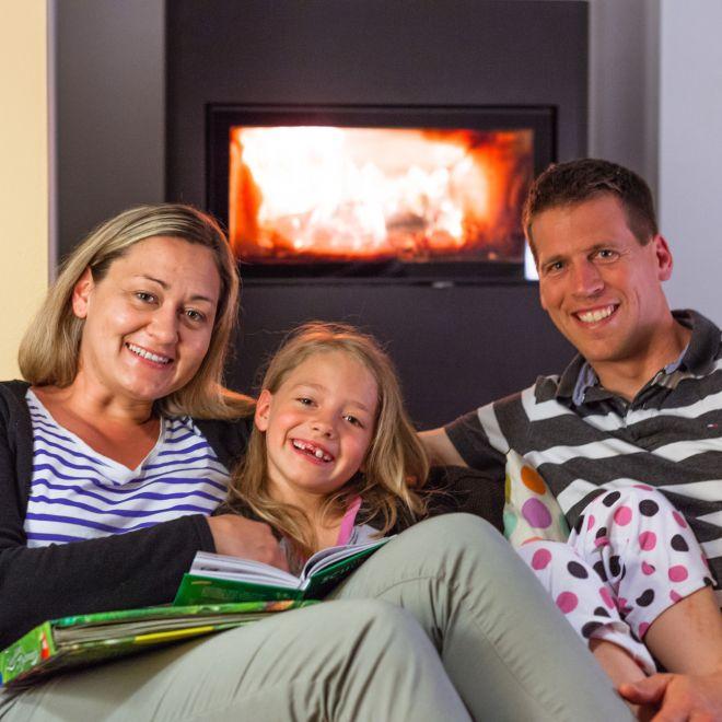 Modernisierungsdarlehen Thüringen (im Bild: Eine Thüringer Familie sitzt gemütlich auf dem Sofa vor dem Kamin)