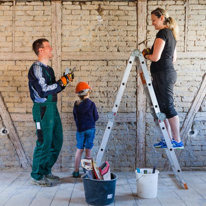 Was muss ich zum Thema Hauskauf und Baufinanzierung wissen? (Im Bild zu sehen: Eine Familie renoviert gemeinsam ihr Eigenheim)