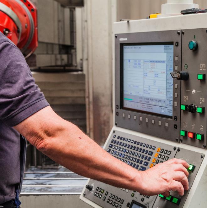 Überbrückungshilfe Corona (im Bild: Mitarbeiter bedient in einer Produktionshalle eine Maschine)