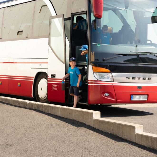 Coronahilfe Schülerverkehr (im Bild: Kinder steigen aus einem Bus aus)